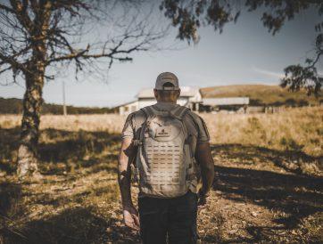 Homem com mochila em campo aberto