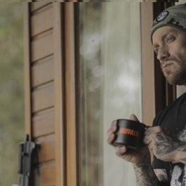 Homem olhando pro lado tomando café, com arma no fundo