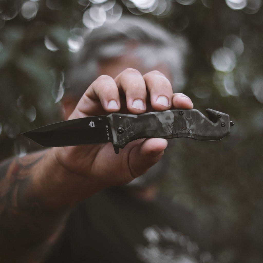 Canivete INVICTUS e ao fundo um operador