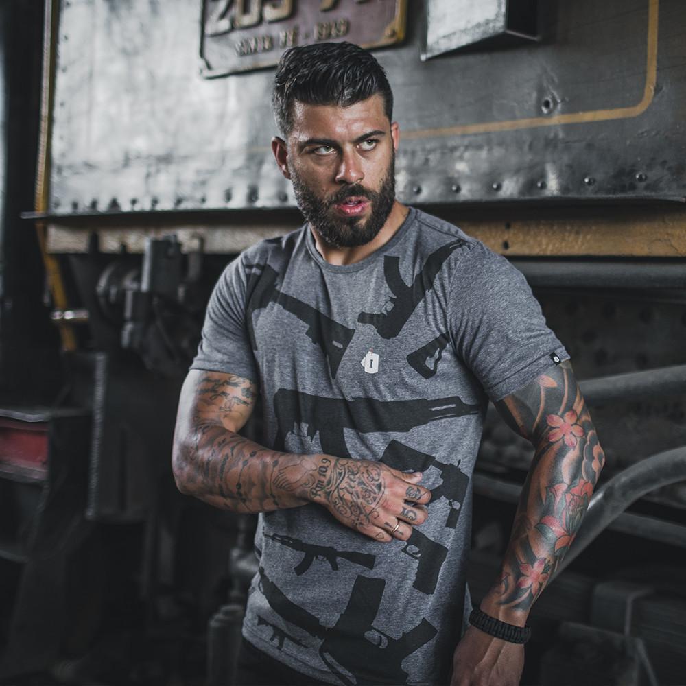 Homem tatuado com camiseta tática