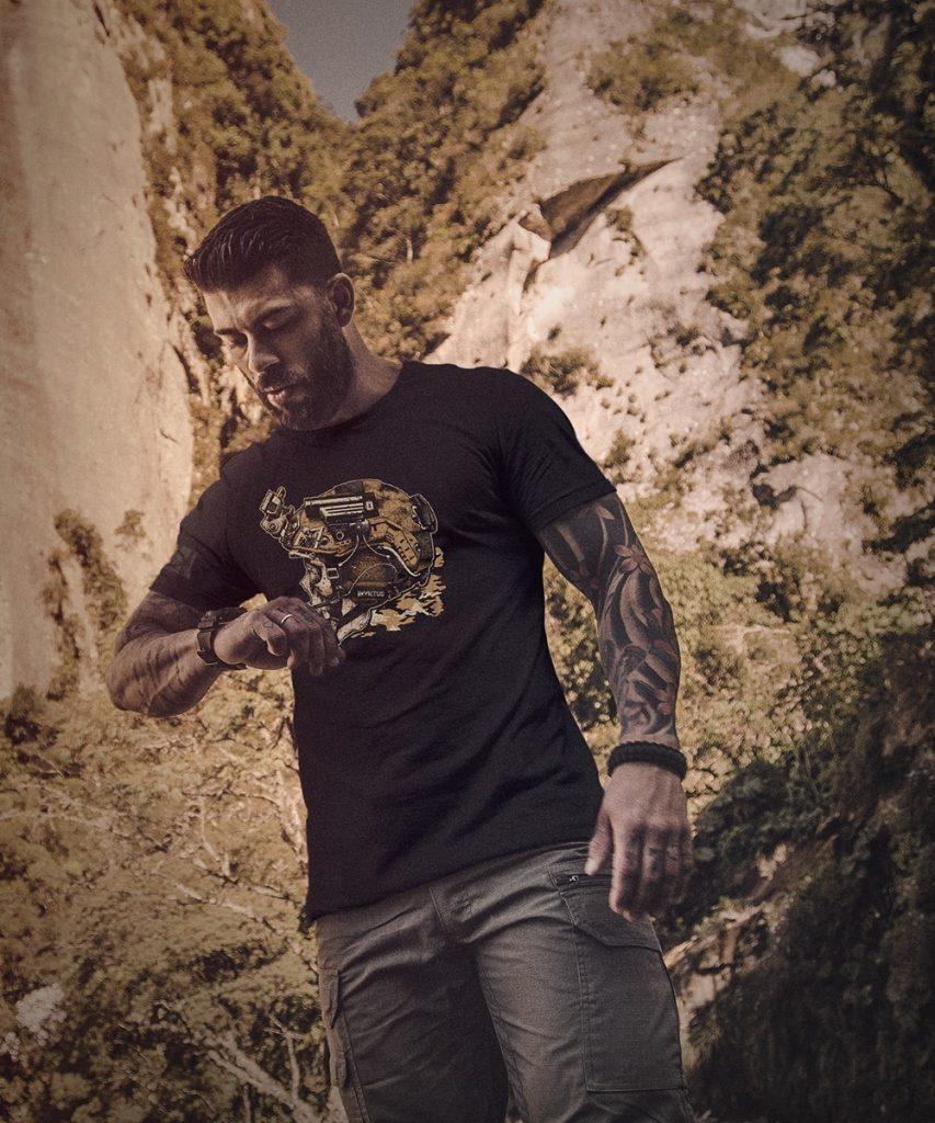 homem tatuado olhando o relógio no meio da natureza