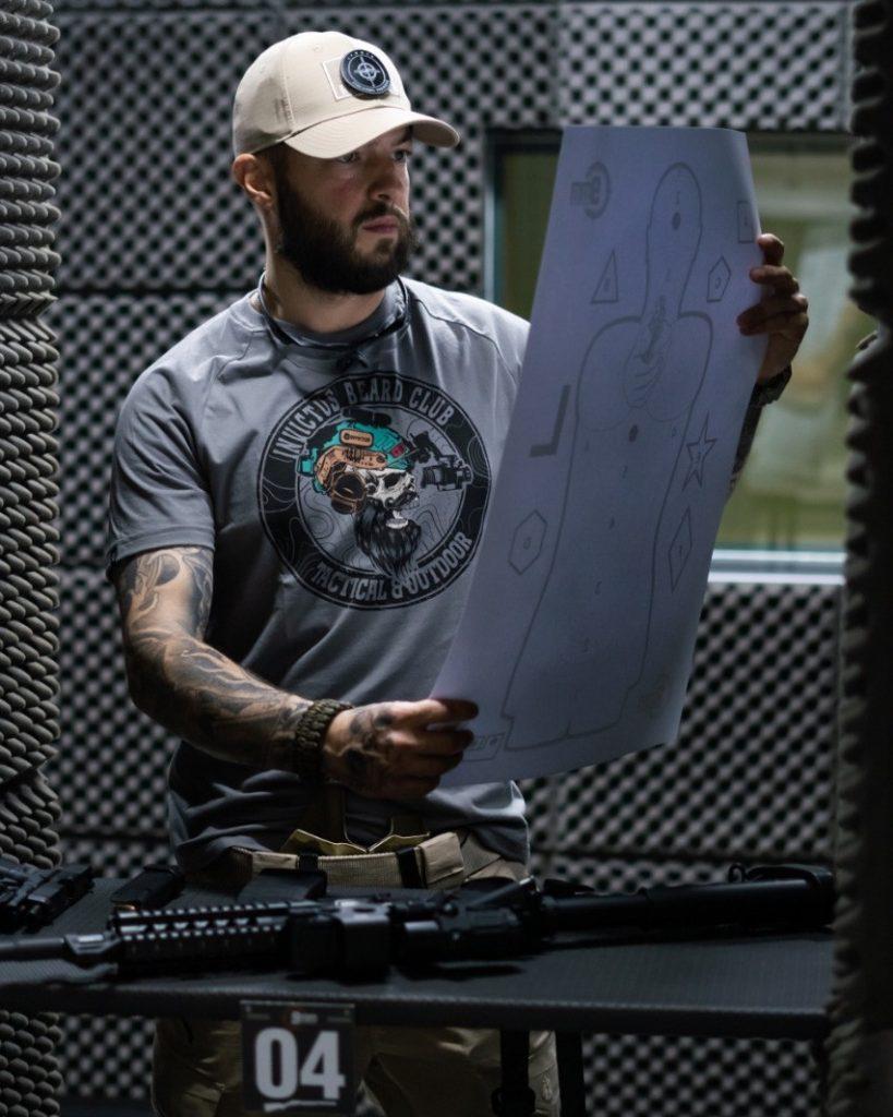 Homem vendo um alvo móvel junto num clube de tiro indoor