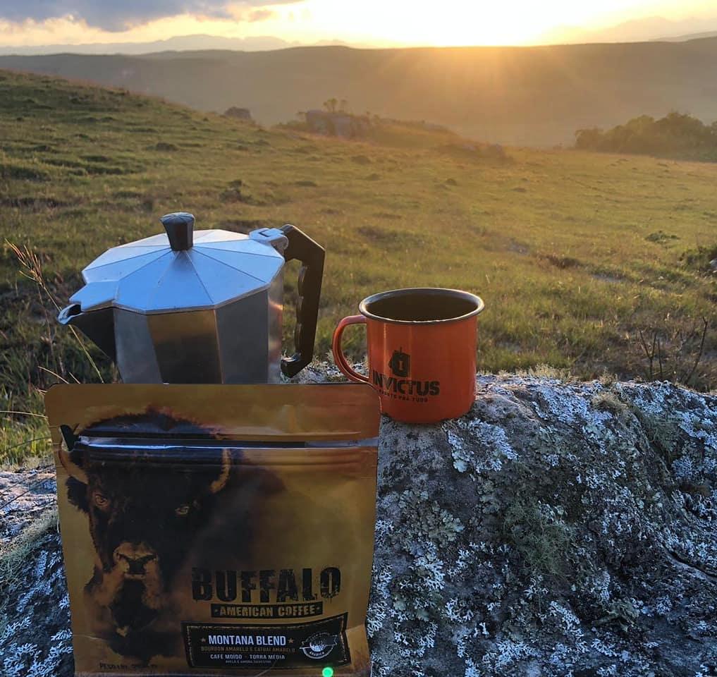 amanhecer com café, com uma caneca, uma cafeteira e uma embalagem de café num meio outdoor.